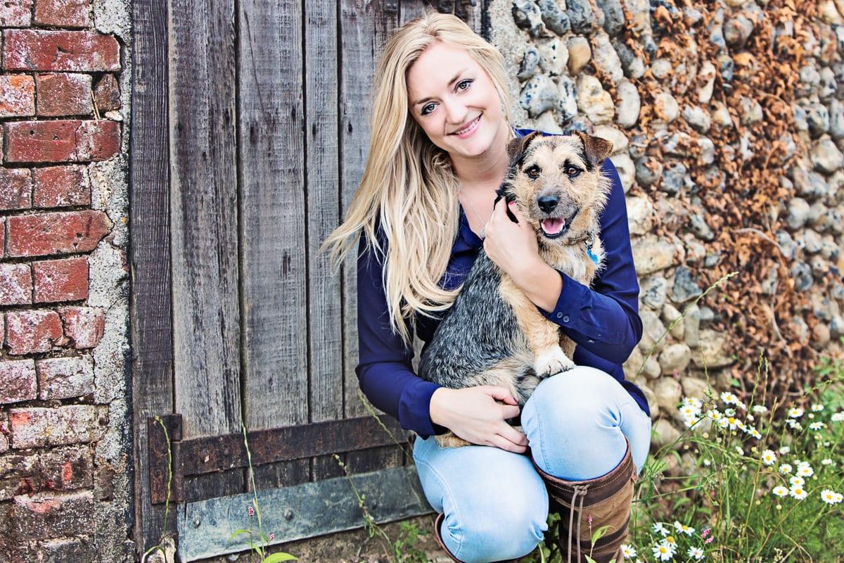 Terrier cross with his owner in front of a barn door.