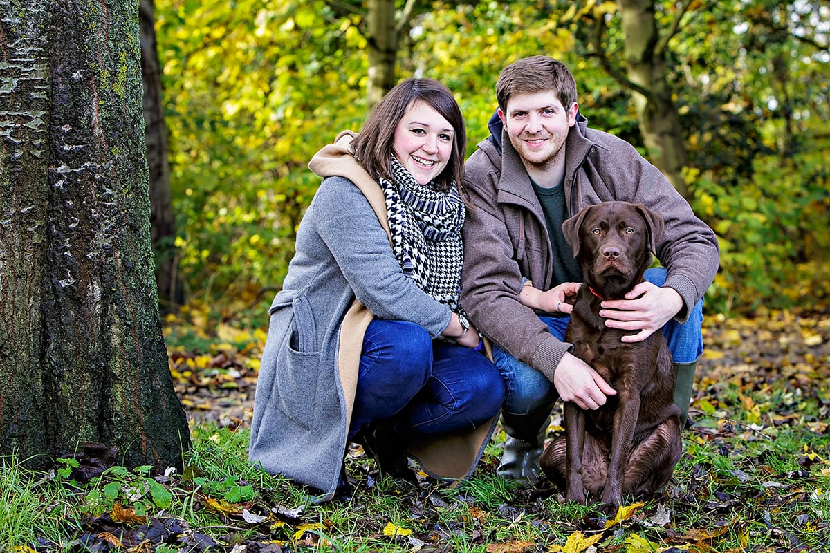 Chocolate Labrador and his family, sat in the woods.