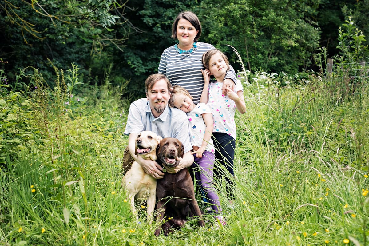 A family portrait with their two labradors in the grass.